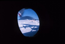 A last look at South Pole Station out a window of the C-130