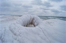 Wave action and arctic air combine to sculpt this ice volcano.