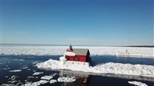 The Grand Haven Lighthouse partially covered in ice. This is where the Grand River reaches Lake Michigan.