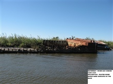 Rusted work barge aground on the bank
