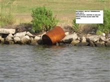 Rusted 55 gallon drum sitting along side the canal
