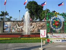 A celebratory float for a parade to be held at Rizal Park with a mural in thebackground.