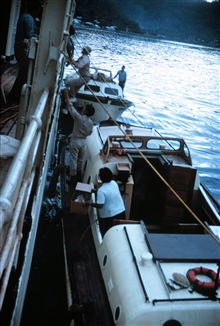 The end of a survey day.Passing the fathometer records to the survey techs for scanning.Lt. Theberge passing records, Lt. Fred Jones climbing ladder.Operations on NOAA Ship SURVEYOR
