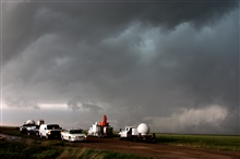 A fleet of VORTEX2 vehicles tracks a supercell thunderstorm near Dumas.The blue-green color in the cloud is associated with large hail.