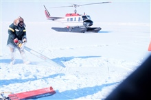Helicopter operating in Beaufort Sea area.  Scientist cutting hole in ice toconduct under-ice dive operations.