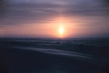 A sun pillar forms as the sun rises over the Arctic plain