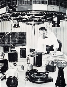 Scientist inspecting early TIROS satellite components.  In the immediateforeground are two TV cameras with a tape recorder in between.