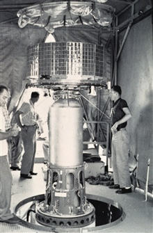 Mounting early TIROS satellite on nose of rocket prior to launch.  TIROSsatellites were 18-sided polygons, 22 1/2 inches high with a 42-inch diameter.They weighed between 270 and 300 pounds.
