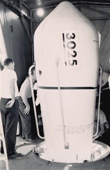 Securing cover for TIROS V satellite prior to launching.  Lettering on nosecone reads:  CAUTION EXPLOSIVE DEVICES ARE SET IN THIS VEHICLE CONSULTDIRECTIONS BEFORE HANDLING.  The bulbous nose fairing protected the satelliteduring its ride through the