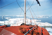 Bow of orange painted survey launch picking its way through ice bergs