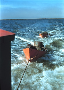 Survey launch towing dinghies after supplying observing camp