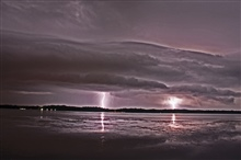 Lightning in the distance seen over bay waters.
