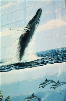 Building mural with humpback whale breaching and a dolphin below.