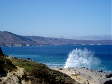 Waves crashing into Santa Rosa Island produce an arc of spray.