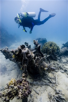 Diver investigates the anchor windlass at the OSHIMA shipwreck site.