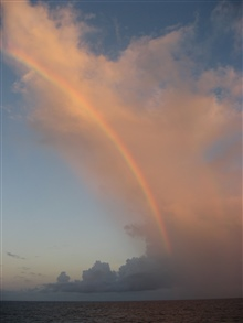 A spectacular late afternoon rainbow following the arc of a cloudformation