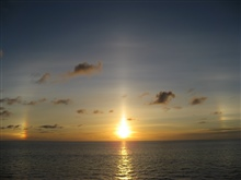 Sunset at sea with sun dogs on each side of the setting sun