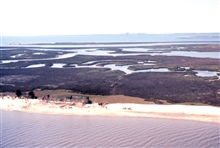 Grand Bay National Estuarine Research Reserve.West from Grand Bay showing large shell midden, Point aux Chenes Bay, and Chevron sour-oil refinery five miles in background on western border of NERR. LSU aerial shoreline survey of October 1998.