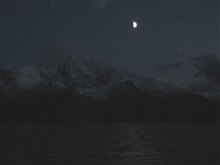 Night-time cruising in the Aleutian Islands. Moon beams reflecting off the water as mountains are barely perceptible in thedistance.