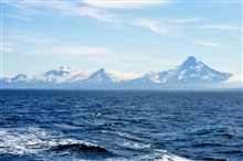 Roundtop is the high mountain on the left, the next is an unnamed peakdesignated Unimak 5270 by the Alaska Volcano Observatory, and Isanotski,locally known as Ragged Jack is on the right.  This view is from the BeringSea.