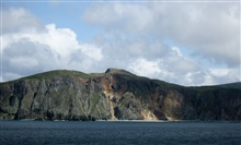 The rugged shores of the Shumagin Islands.  A narrow strip of rocky beachbefore nearly vertical cliffs.