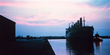 A large break-bulk merchant vessel docking at sunset at Lake Charles.