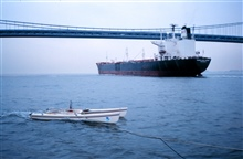 An outbound ship passes under Verrazano Narrows Bridge as a NOAA modifiedcatamaran takes mobile current profiles with an acoustic data collectionplatform (ADCP).