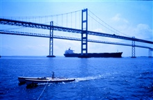 A modified catamaran takes mobile current profiles with an acoustic digitalcurrent profiler (ADCP) as a large bulk carrier passes under the ChesapeakeBay Bridge heading up the bay.