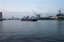 Tug pushing barge down the Elizabeth River with Norfolk skyline andshipyard in picture.