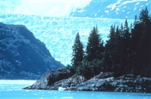 A glacier looming above a rocky point