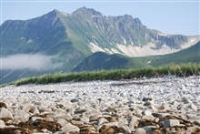 Looking over a boulder beach to rugged mountains of the Alaska Peninsula.Dakavak Bay.