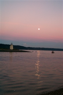 Moonrise over Gig Harbor as salmon fishermen try their luck in the shallows offthe spit. Mt. Rainier is visible in the left center.