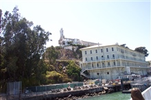 The pier at Alcatraz.  The lower building housed guards and workers while theprison is on the top of The Rock.  The high tower is a Coast GuardLighthouse and the ruined building on left is the remains of the warden's home.