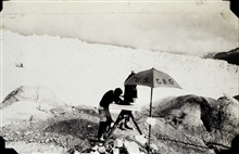 L. S. Hubbard at plane table in glacial area.Off of SURVEYOR