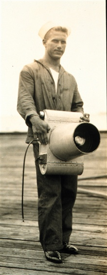 Navy crewman holding K-1 camera.Used on Mississippi Delta mapping project