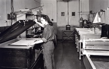 Woman operating photo-reproduction equipment