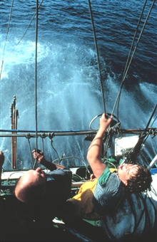One fisherman holds the pole from the deck while another, higher up, pulls theattached cord when the tuna takes the bait.