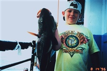 A young fisherman proudly displays a fish almost as large as himself.Aboard the headboat YANKEE PATRIOT out of Gloucester.