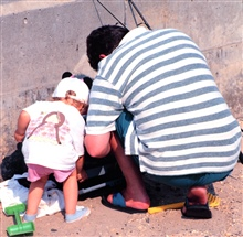 Daddy's helper assists in preparing tackle while fishing at Manasquan Inlet.