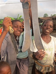 Kids from local Sao Tomean fishing village displaying their machetes
