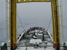 AMLR scientists and Russian crew peer over the bow of the R/VYuzhmorgeologiya as the ship slowly makes it way through icy watersin an Antarctic snowstorm.