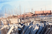 Human labor construction site with wood scaffolding