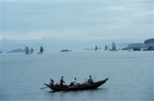 Rowed fishing vessel with sampans in distance
