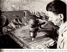 Relief model - a thin gauge aluminum sheet - is formed on the BraundReliefograph.  The altimeter is seen on the left.In: Wilson, Don C. 1949. Production of Plastic Relief Maps in Surveying andMapping, Vol. IX, no. 3, pp. 183-186.