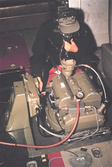 Aerial photographer in unpressurized cabin of NOAA de Havilland Buffalobreathing with assistance of oxygen mask, operating Wild RC-8 camera.