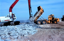 A large crane places rock in the dump truck at the construction site.