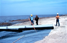 Brian Kendrick, Chris Gray and a Bertucci representative standing by roles offilter cloth and geogrid on the beach.