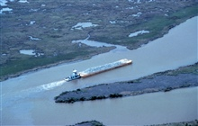 An aerial view of the tug pushing a barge load of rock up Locust Bayou.