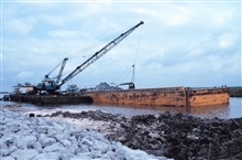 A barge-mounted crane loading rock at the construction site.