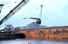 A barge mounted crane loads rock at the construction site.